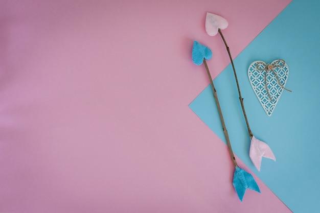 Flechas de la ramita del día de tarjetas del día de san valentín en fondo rosado y azul con el corazón
