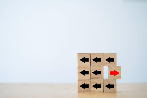 Una de las flechas rojas se mueve en dirección opuesta con otras flechas negras talladas en cubos de bloques de madera para la interrupción del negocio y el concepto de idea de pensamiento diferente.