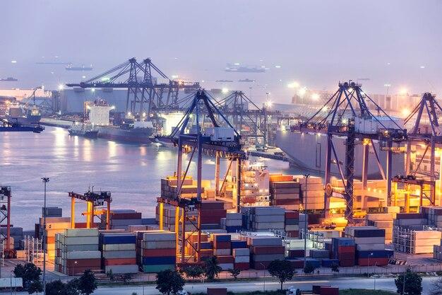 Flete de carga de contenedores con grúa de trabajo bridgeat anochecer para logistic import export b