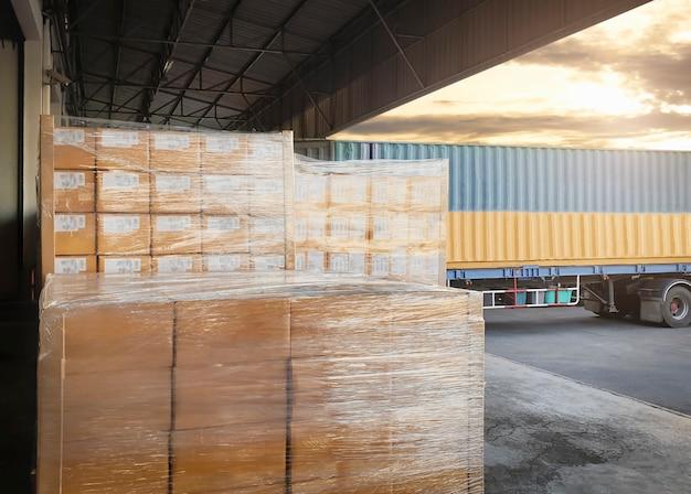 Flete de carga, embarque, embarque, delivery, logística y transporte de mercancías. grandes paletas de mercancías esperando su carga en un contenedor de camión.