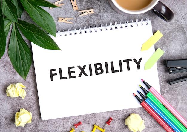 Flexibilidad en un cuaderno con una taza de café, hojas comprimidas, crayones y engrapadora