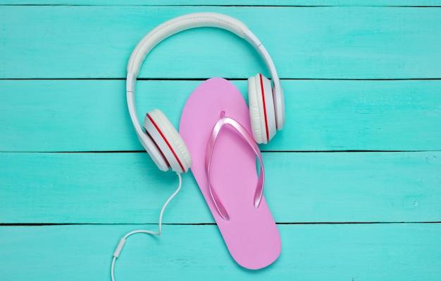 Flip flop y auriculares sobre fondo de madera azul. el verano relájese. vacaciones de verano. belleza y moda.