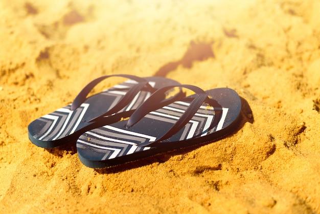 Flip-flop de verano en la playa de arena del mar. concepto de vacaciones tropicales