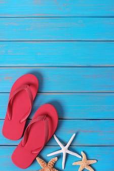 Flipflops estrella de mar verano costa azul madera fondo de madera vertical