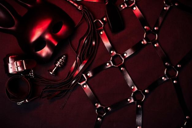 Flogger de cuero, esposas, cinturón, gargantilla, máscara y tapón anal de metal para bdsm