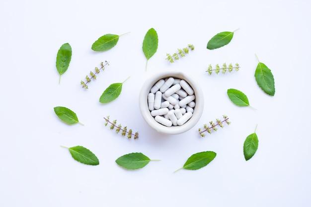 Flor de albahaca santa y hojas con pastillas de medicinecapsules hierbas sobre fondo blanco