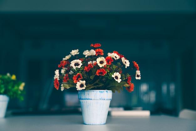 Flor artificial colorida del ramo en florero en la tabla moderna.