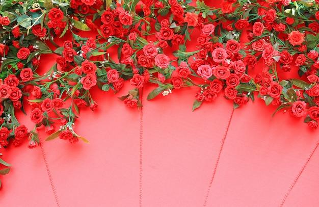 Flor artificial de la rosa del rojo en fondo rojo de la textura de la lona.