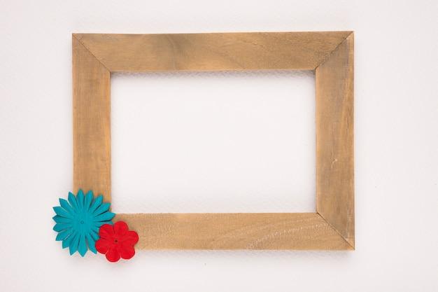 Flor azul y roja en la esquina del marco vacío de madera aislado sobre fondo blanco