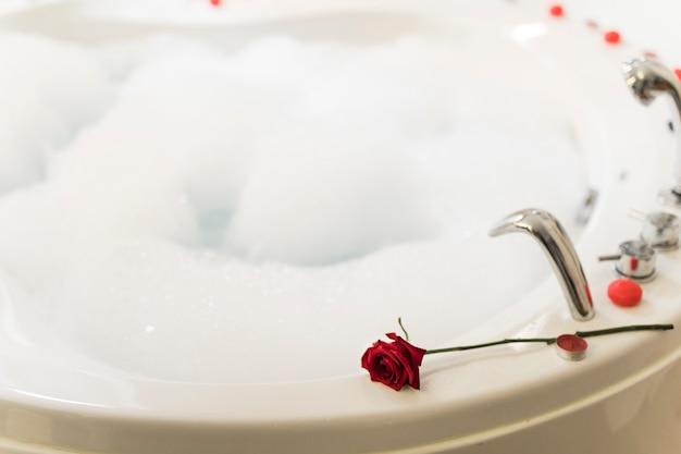 Flor en bañera de hidromasaje con agua y espuma.