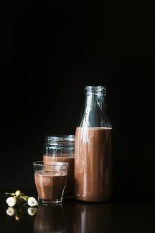 Flor con batido de chocolate en botella; vaso y jarra sobre fondo negro