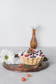 Flor blanca y deliciosas mini tartas con bayas frescas en bandeja de madera para servir