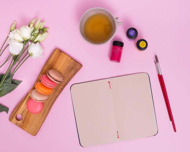 Flor blanca eustoma; macarrones; taza de té de hierbas; pincel y botellas de pintura cerca de la libreta en blanco sobre fondo rosa