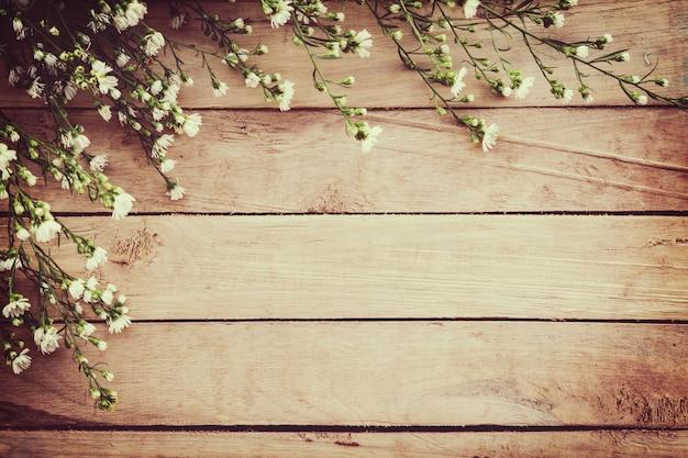 Flor blanca en el fondo del tablero de madera del grunge con espacio.