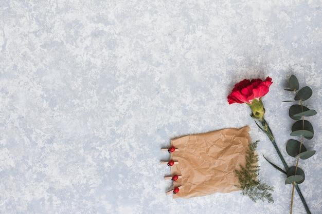 Flor de clavel con papel en blanco sobre mesa