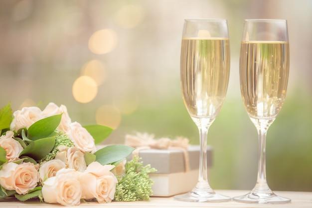 Flor color de rosa, caja de regalo, copa de vino, en mesa de madera con bokeh