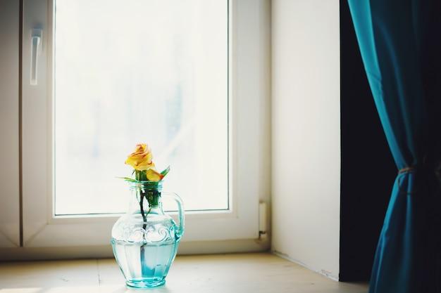 Flor color de rosa en florero azul junto a la ventana