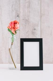 Flor colorida en florero cerca del marco en blanco en la tabla