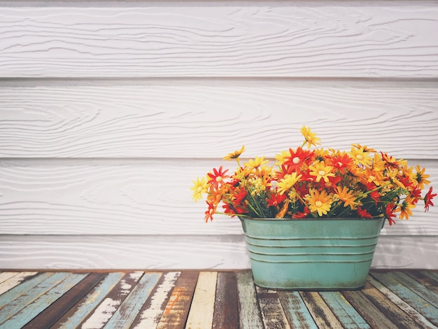 Flor colorida en florero vintage sobre mesa de madera