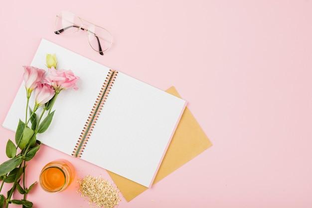 Flor en un cuaderno abierto; los anteojos; jarra de jugo y muesli en fondo rosado