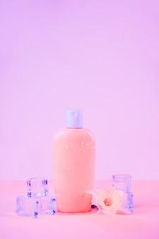 Flor con cubos de hielo de cristal con frasco de protección solar sobre fondo rosa