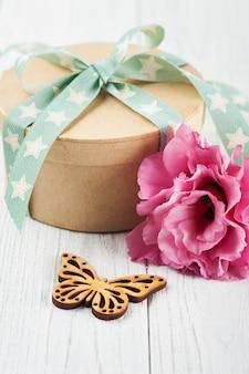 Flor de eustoma y caja de regalo con cinta verde estrella