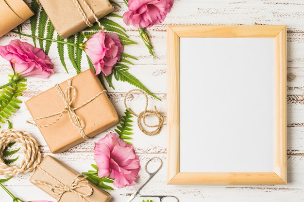 Flor de eustoma y regalos empaquetados con marco vacío en mesa.