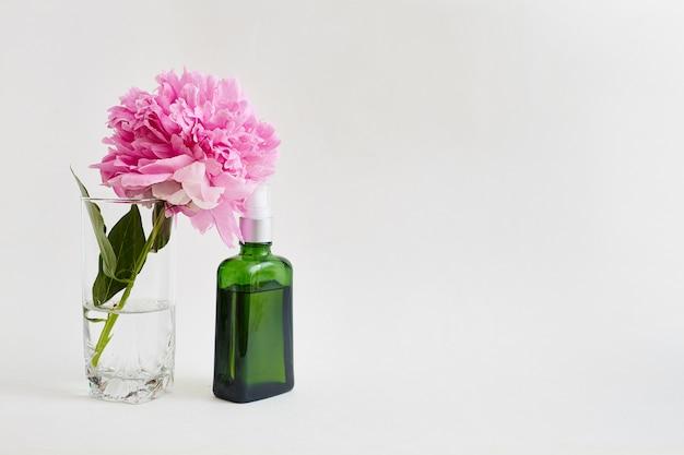 Flor y frasco de vidrio verde con aceite corporal.