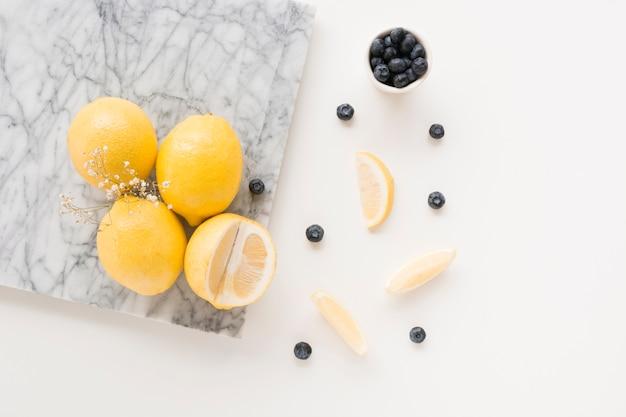Flor de gypsophila con limones y arándanos sobre fondo blanco
