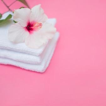 Flor de hibisco blanco y toallas sobre fondo rosa