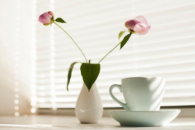 Flor de jarra y taza de café con platillo cerca de la persiana de la ventana