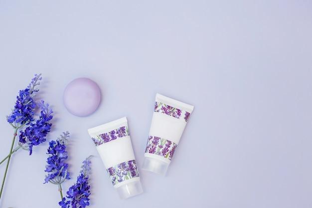Flor de lavanda falsa; jabón y crema hidratante sobre fondo coloreado.