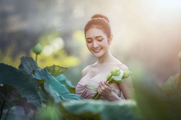 Flor de loto asiática de la cosecha de la mujer en el jardín, tailandia.