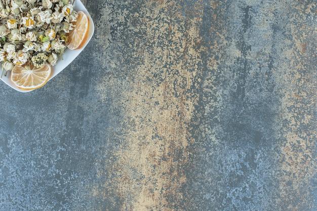 Flor de manzanilla seca en un tazón blanco.