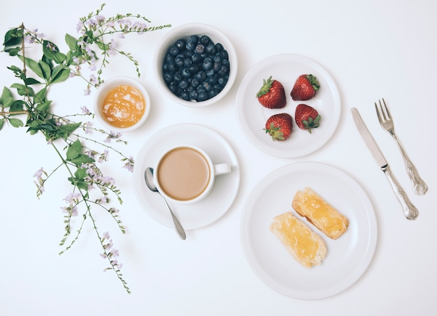 Flor; mermelada; arándano; fresa; taza de café y pan tostado sobre fondo blanco con cubiertos