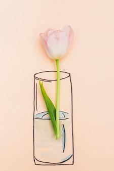 Flor natural colocada en florero pintado.