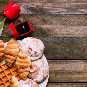 Flor, panadería en plato y anillo en caja de regalo.
