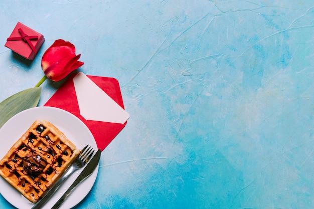 Flor, panadería en plato con cubiertos, caja de regalo y sobre