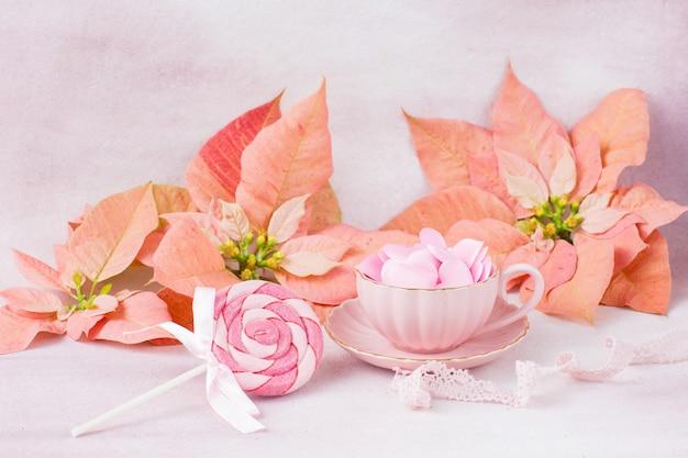 Flor de pascua rosa, dulces en palitos y corazones rosados de satén en una taza rosa