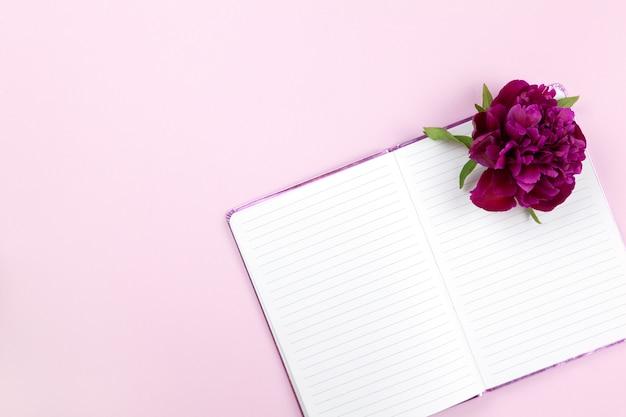 Flor de peonía en el bloc de notas sobre fondo rosa pastel