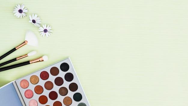 Flor; pinceles de maquillaje y paleta de sombras de ojos sobre fondo texturizado de menta