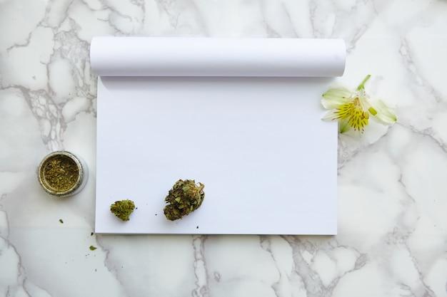 Flor y porro de cannabis con thc / cbd en el bloc de notas de dibujo