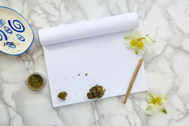 Flor y porro de marihuana con thc y cbd en un cuaderno de dibujo