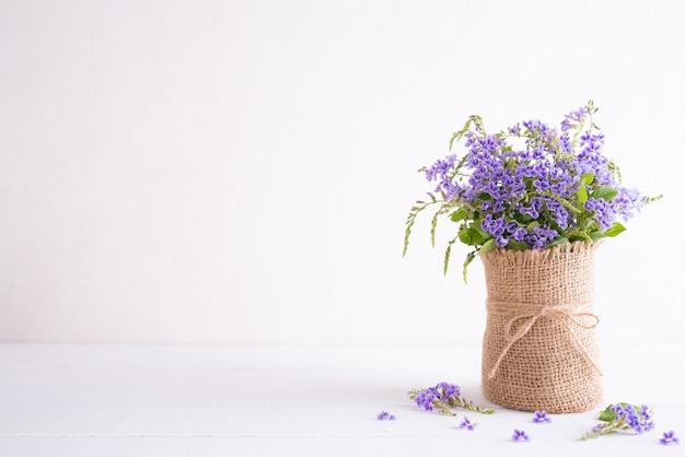 Flor púrpura preciosa en florero del saco en la tabla de madera blanca.