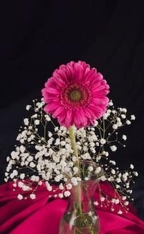 Flor con ramitas en flor en florero cerca de textil color de rosa en la oscuridad