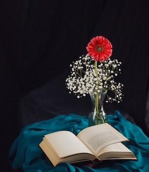 Flor con ramitas de flores en un jarrón cerca del volumen y textil azul en la oscuridad
