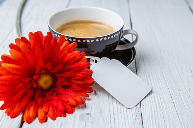 Flor roja, taza de café en la mesa blanca con tarjeta limpia