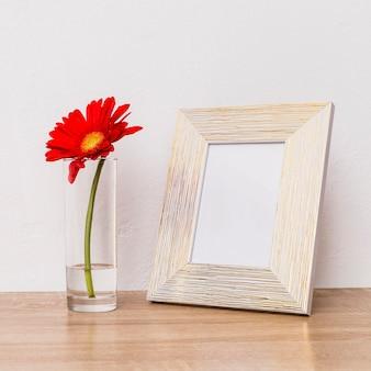Flor roja en vidrio y marco de fotos en mesa