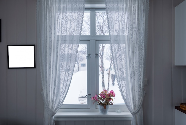 Flor rosa en el alféizar de la ventana con cortina y marco de fotos en la temporada de invierno