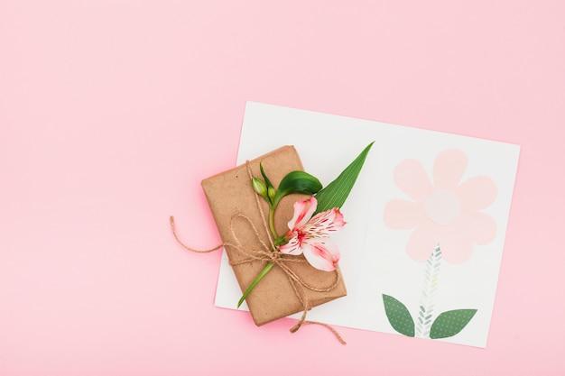 Flor rosa con caja de regalo en mesa rosa